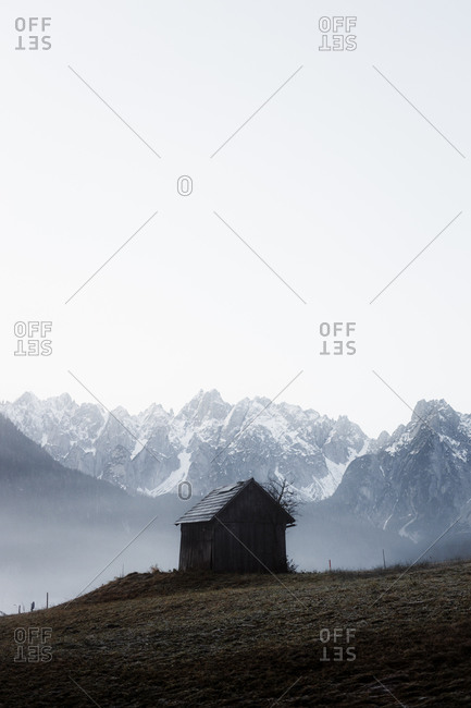 Small wooden hut located on grassy slope against foggy rocky mountain range under gray sky in gloomy autumn weather