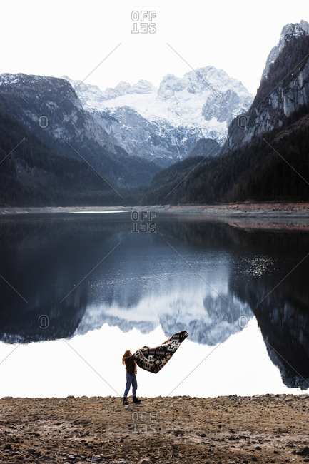 Distant unrecognizable female hiker with blanket in outstretched arms standing on shore of calm lake with smooth water surface reflecting rocky mountains covered with snow in overcast autumn day