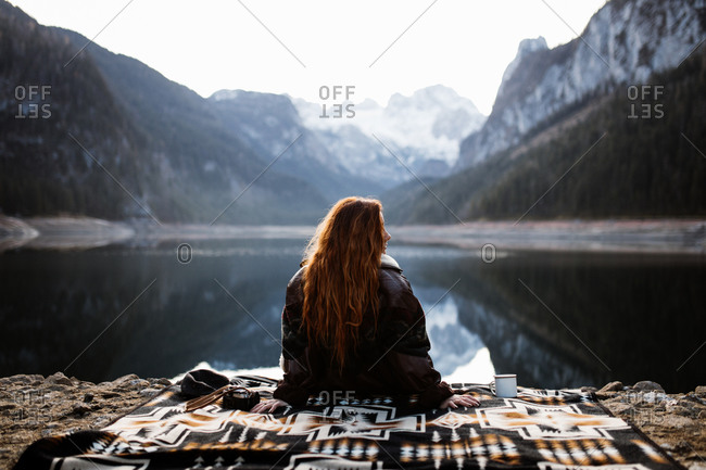 Back view of unrecognizable female traveler sitting on blanket near calm lake surrounded by majestic rocky mountains covered with forest and snow and enjoying silence in autumn morning