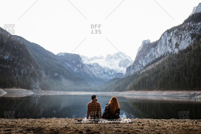 Back view of unrecognizable couple in warm clothes sitting on shore of peaceful lake and enjoying spectacular landscape of snowy mountains in autumn morning