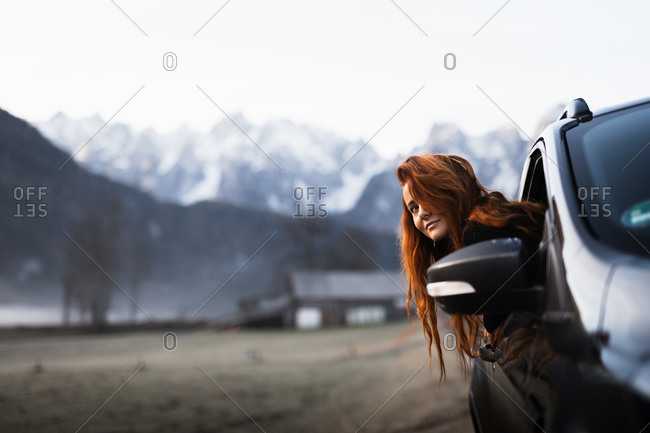 Side view of young female tourist looking out from open window of car while travelling through autumn countryside with rocky mountains covered by snow