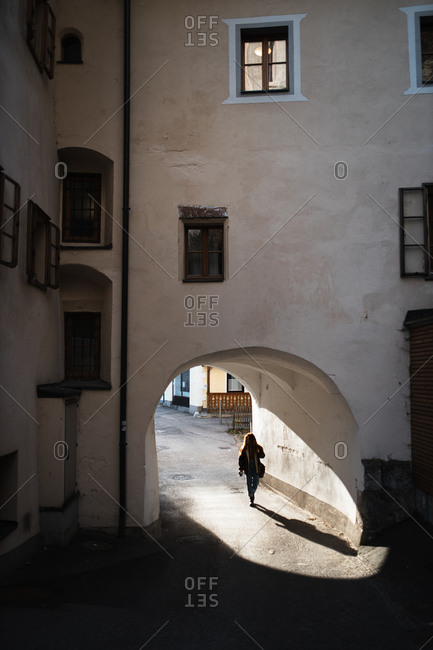 From above back view of unrecognizable female traveler walking through archway of aged stone building in old town