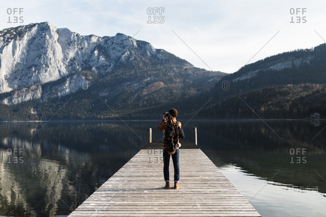 Back view of unrecognizable male tourist in warm outfit standing on wooden boardwalk and taking picture of amazing scenery of lake surrounded by rocky mountains in autumn day