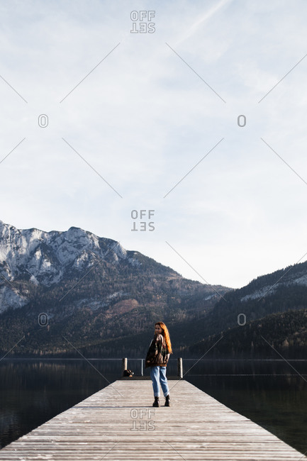 Back view of lonely female traveler standing on wooden pier near lake with snowy rocky mountains on shore in sunny autumn day