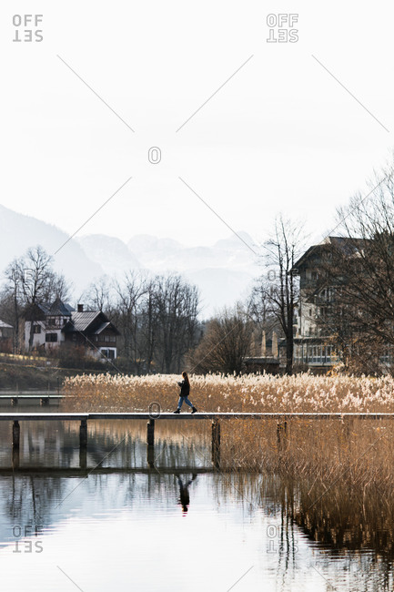 Side view of unrecognizable person walking on wooden boardwalk over calm lake with grassy shore in small settlement located in mountainous terrain in autumn day