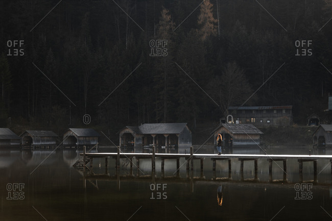Distant unrecognizable female tourist walking on wooden pier near tranquil lake with wooden sheds on shore against dark coniferous forest