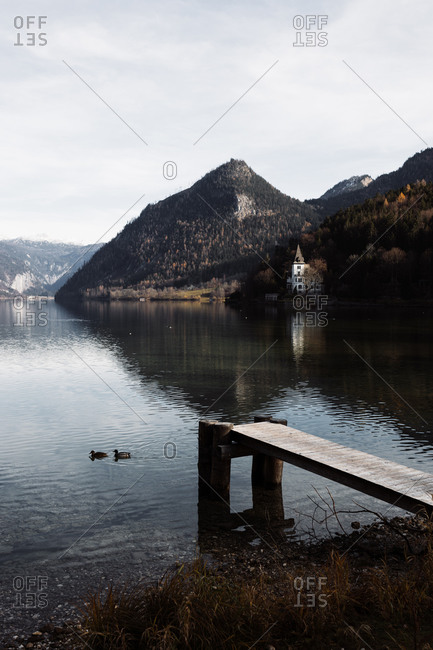 Magnificent scenery of peaceful lake with couple of ducks floating near wooden pier and lonely building located on shore against rocky mountains in cloudy autumn day