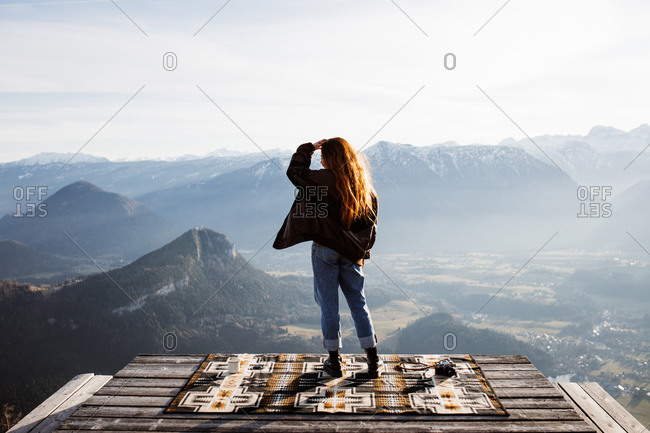 Back view of unrecognizable female tourist standing at viewpoint in mountains and observing amazing scenery in morning