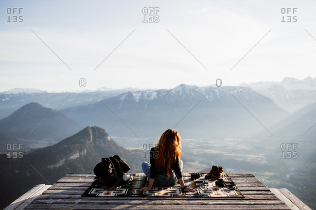Back view of unrecognizable female tourist sitting at viewpoint in mountains and observing amazing scenery in morning