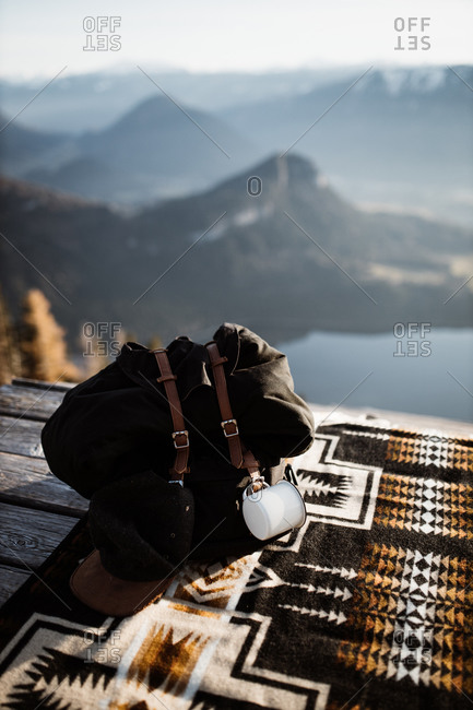 Backpack and retro photo cameras placed on blanket on wooden terrace on background of mountainous landscape
