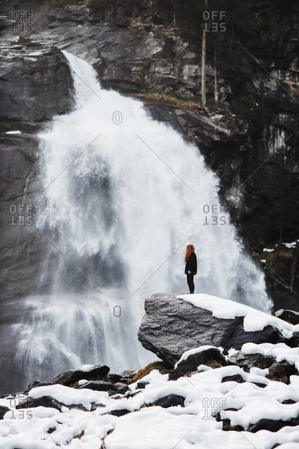 Side view of traveling woman standing on rock and observing amazing view of powerful waterfall in highlands in winter
