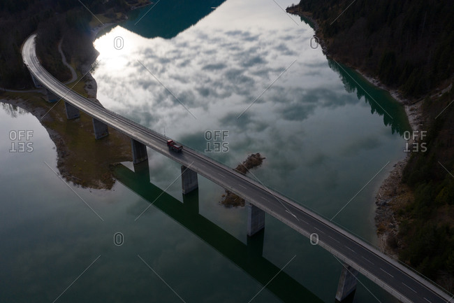 Drone view of truck driving along suspension bridge over calm river in autumn