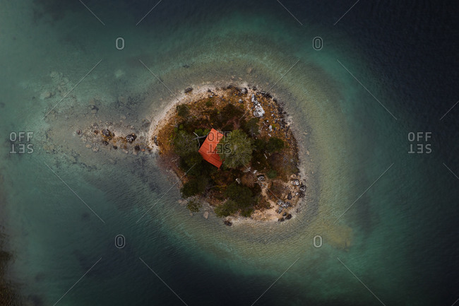 Drone view of breathtaking scenery of small house located on island in calm sea