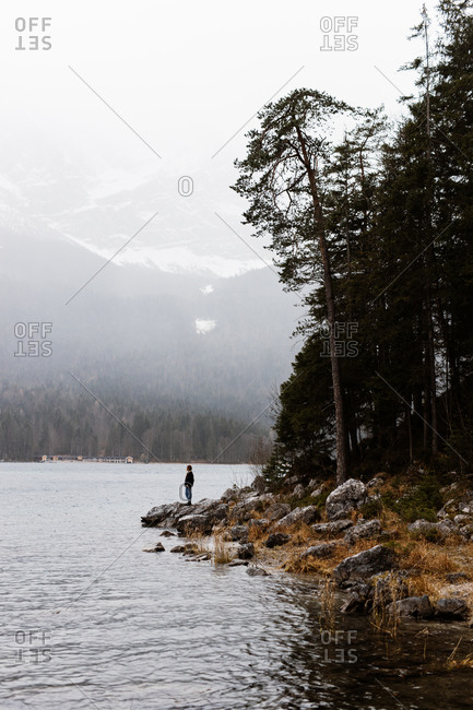 Distant traveler standing on rocky shore near pond and admiring scenery of highlands in winter