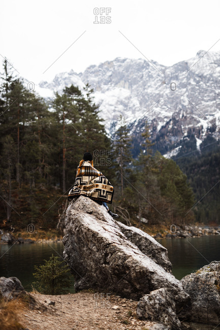 Back view of unrecognizable tourist sitting on stone on shore of pond and observing mountains covered with snow in winter