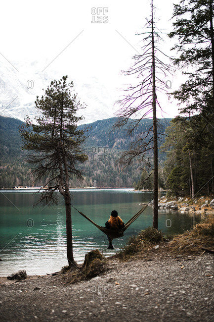 Back view of serene female traveler sitting in hammock and enjoying majestic view of lake in mountains in autumn