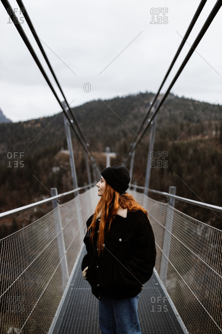 Female tourist in warm clothes walking along metal suspension bridge in highlands and enjoying vacation in autumn