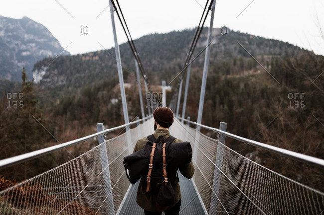 Back view of male tourist in warm clothes walking along metal suspension bridge in highlands and enjoying vacation in autumn