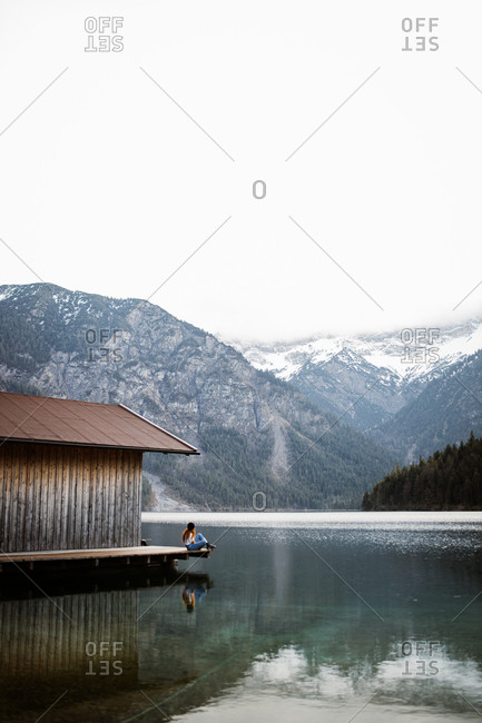 Side view of unrecognizable female sitting on wooden quay and enjoying scenery of calm pond and mountains covered with snow in winter