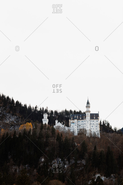 Magnificent scenery of historic castle with towers located on hill in forest in mountainous area in autumn