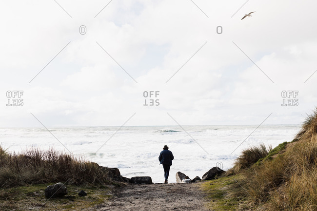 Back view of anonymous male tourist walking along beach towards stormy sea on cloudy day
