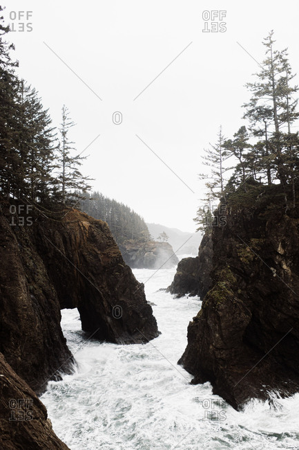 Fast river flowing through rough rocky terrain in mountainous area under overcast sky in autumn
