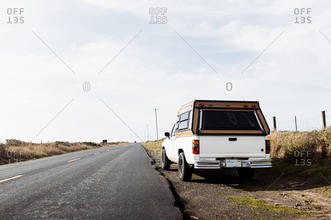 Modern automobile parked near asphalt road in countryside on sunny day in autumn