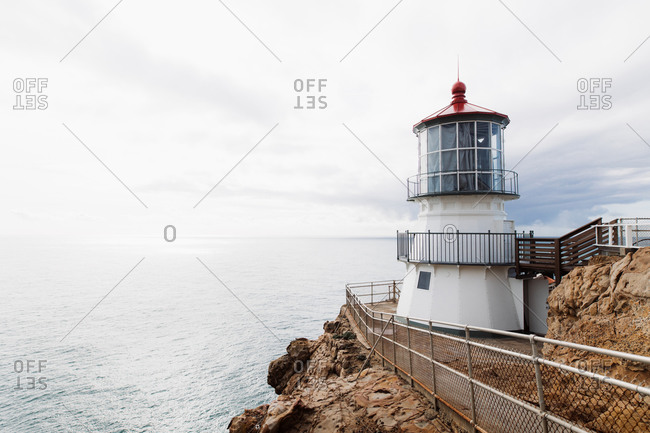 Breathtaking scenery of lighthouse and cabin located on rough rocky cliff on background of calm sea under cloudy sky