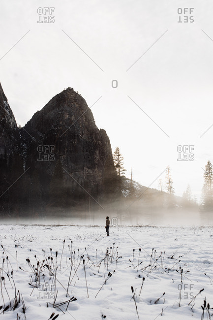 Distant unrecognizable person walking on breathtaking scenery of blizzard in winter in highland area on background of gray sky