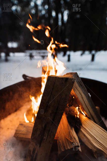 From above camping fireplace with burning firewood in snowy winter day