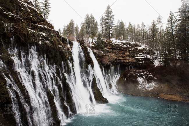 Picturesque scenery of powerful waterfall with pool flowing among snowy forest in mountainous terrain in winter day in USA