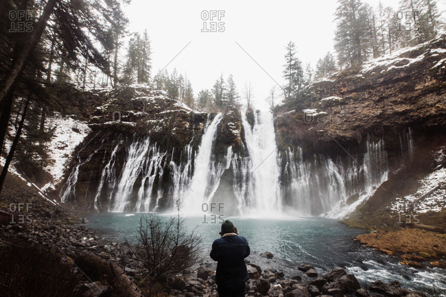 Back view of unrecognizable picturesque scenery of powerful waterfall with pool flowing among snowy forest in mountainous terrain in winter day in USA