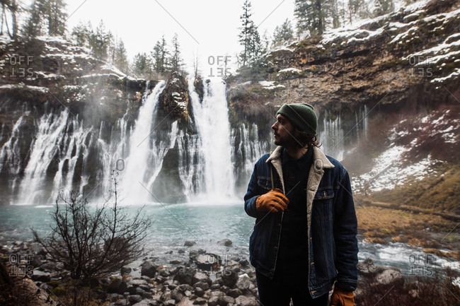 Man standing on picturesque scenery of powerful waterfall with pool flowing among snowy forest in mountainous terrain in winter day in USA looking away