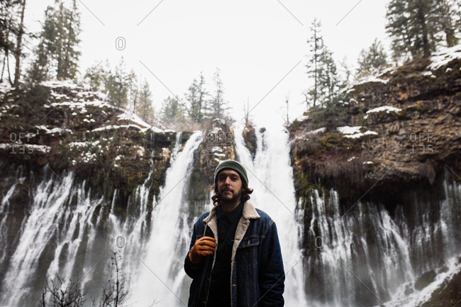 Man standing on picturesque scenery of powerful waterfall with pool flowing among snowy forest in mountainous terrain in winter day in USA looking at camera