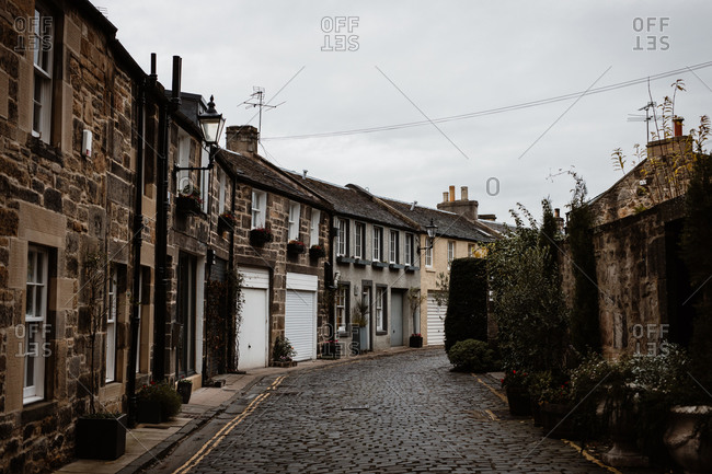Perspective view of old narrow street with grunge residential buildings on background of gray sky in Scottish Highlands
