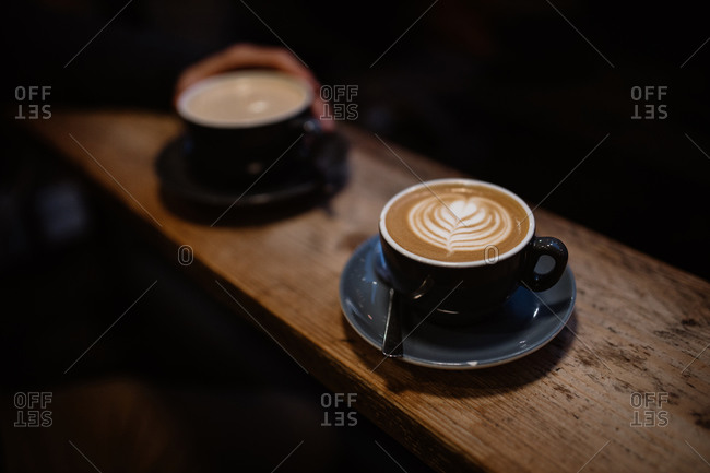 High angle of cup of latte with art placed on wooden counter in cozy coffee house