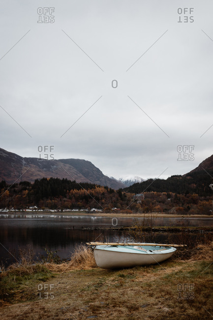 Lonely boat with paddle moored on shore near calm lake on background of mountainous landscape in Scottish Highlands