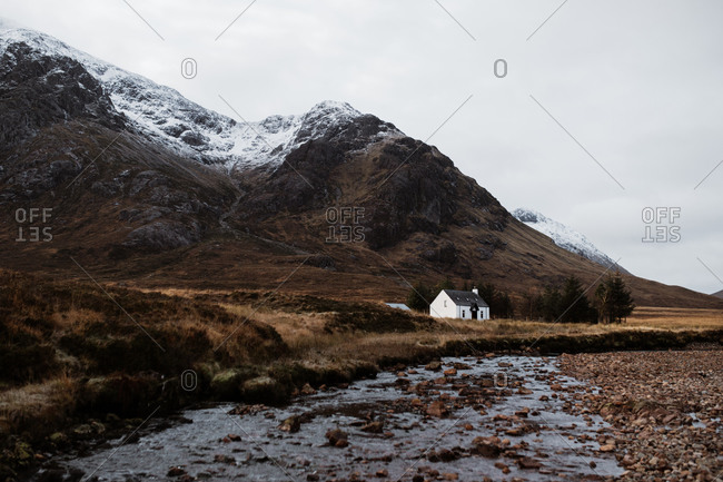 Picturesque view of snowy mountain range and lonely residential house near calm creek under gray sky in Scottish Highlands