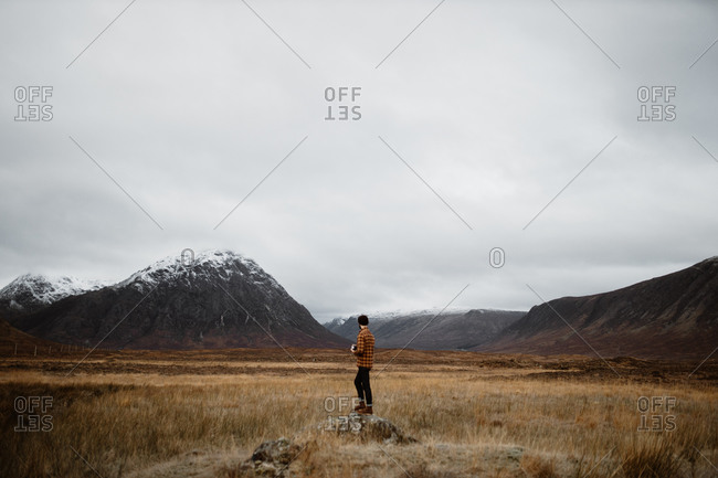 Back view of unrecognizable male explorer standing on rock and enjoying scenery of mountains in fall in Scottish Highlands