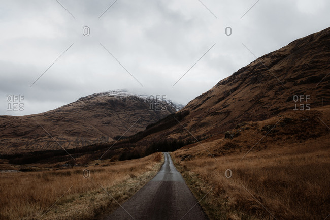 Road in between valley and amazing view of rocky mountain top with snow in fall in Scottish Highlands