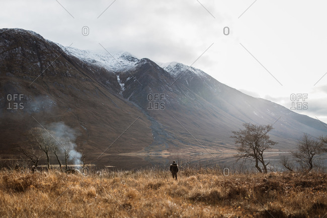 Unrecognizable explorer standing in dry field and admiring spectacular scenery of lake and mountain range in Scottish Highlands in autumn