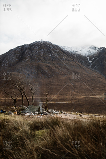 Amazing scenery of camping site with campfire located in mountainous terrain in autumn in Scottish Highlands