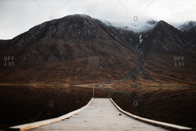 Distant view of lonely tourist sitting on wooden pier and admiring peaceful scenery of mountains and lake on overcast day in Scottish Highlands