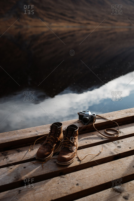 High angle of pair of dirty trekking boots placed on wooden quay near retro photo camera in Scottish Highlands
