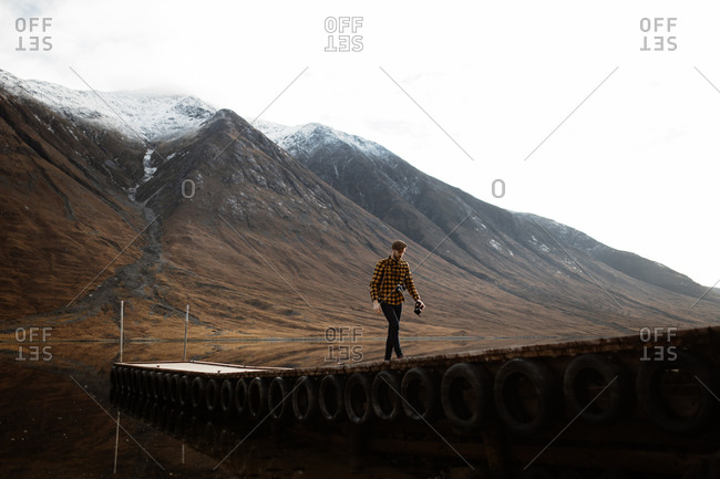 Tourist walking with camera on wooden pier on peaceful scenery of mountains and lake on overcast day in Scottish Highlands