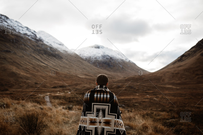 Back view of unrecognizable male explorer standing enjoying scenery of mountains in fall in Scottish Highlands