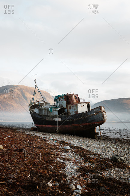 Old rusty fishing boat moored on beach in foggy morning in Scottish Highlands