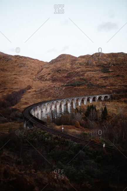Breathtaking scenery of winding Glenfinnan Viaduct leading through mountains in Scottish Highlands in autumn