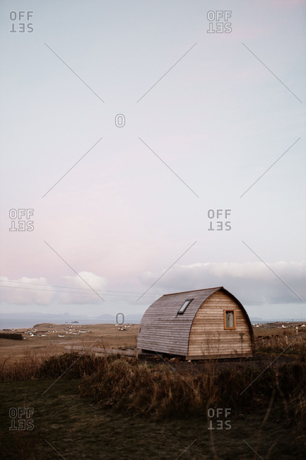 Small wooden house located on dry meadow in countryside at dawn in Scottish Highlands