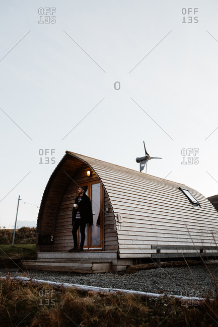 Side view of tranquil male tourist covered with blanket standing on entrance of wooden cottage cabin looking away while enjoying a cup of coffee during vacation in Scottish Highlands in winter